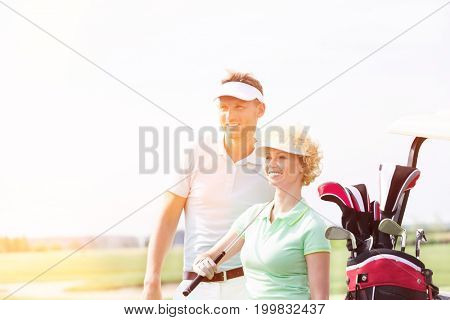 Smiling golfers standing at golf course against clear sky