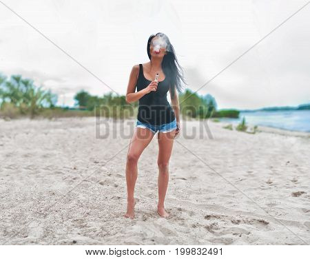 Brunette Girl Smoking Electronic Cigarette On The Beach
