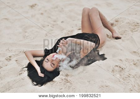 Sexy Brunette Girl Liying On The Beach And Vaping With Vape Mod Device