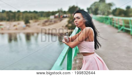 Sexy Brunette Vaping On Bridge. Female Model Vaping Fruit Flavored E-liquid Or E-juice With Vaporize