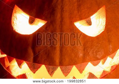 Spooky halloween pumpkin smile with hot burning fire eyes mouth. Big helloween symbol has a glowing closeup mad face and smiling with sharp teeth and bad look. Black orange nightmare of October 31st.