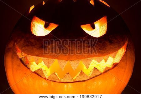 Fat big halloween pumpkin smile with hot burning fire eyes mouth. Spooky helloween symbol has glowing closeup mad face and smiling with sharp teeth and bad look. Black orange nightmare of October 31st.