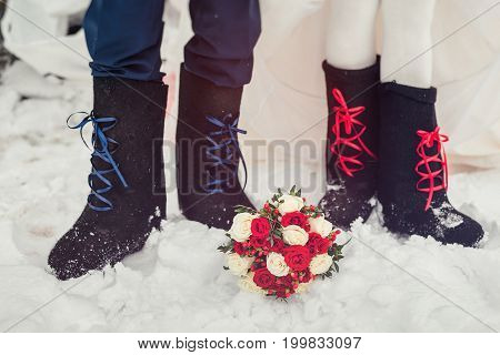 A Closeup Of The Feet Of The Bride And Groom In Felt Boots On Snow Wedding Bouquet. Accessories For