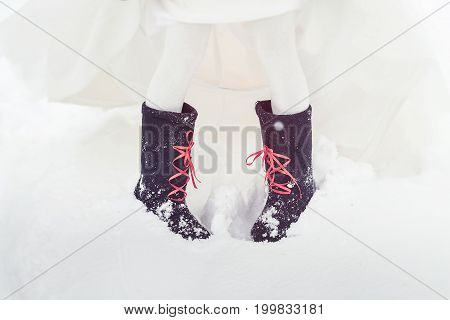 A Closeup Of The Feet Of The Bride In Felt Boots On Snow. Accessories For A Stylized Russian Wedding