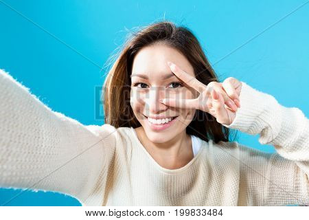 Young woman taking a selfie on a blue background