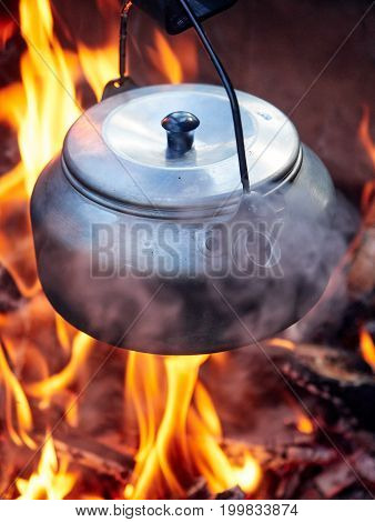 Metallic coffee pot in campfire heat while hiking. Wood burning with flames beneath the pot.