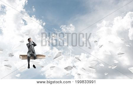 Young shocked businessman sitting on old book and covering eyes with palms