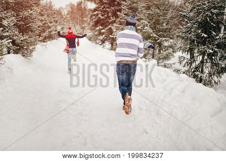 Snowball Fight. Winter Loving Couple Having Fun Playing Catch Up Outdoors. Young Joyful Happy Couple