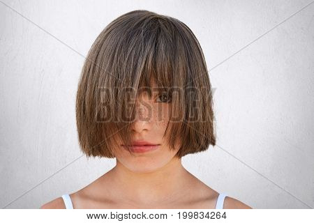 Horizontal Portrait Of Little Freckled Female Child Covering Her Face With Hair While Poising Agains