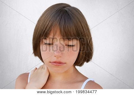 Close Up Of Attractive Little Child With Freckles And Dark Short Hair Keeping Her Hand On Neck, Look