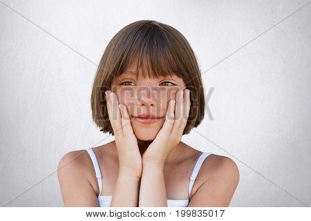 Close Up Portrait Of Adorable Freckled Girl With Bobbed Hairstyle, Keeping Her Hands On Cheeks, Havi