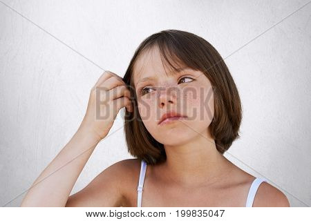 Serious Little Freckled Child, Keeping Her Hand On Hair, Havin Thoughtful Expression, Looking Aside.