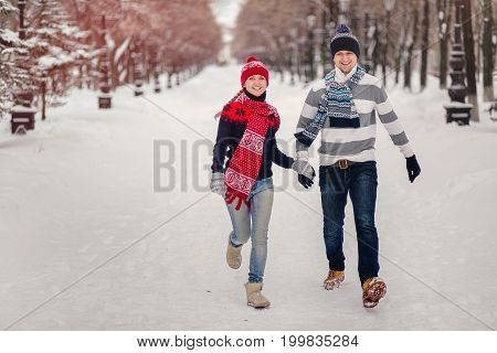 Happy, Young Couple Runing In Snowy Winter Park.