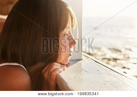 People, Children, Relaxation, Calmness Concept. Adorable Kid Leaning At Wooden Deck, Looking Ar Sea
