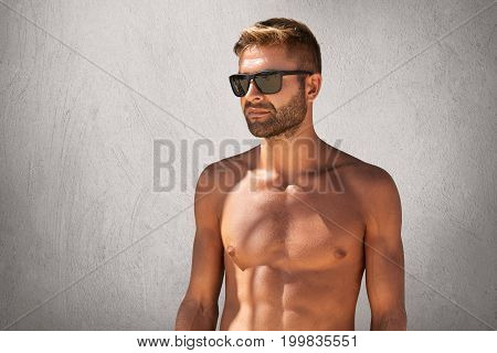 Waist Up Portrait Of Attractive Macho Man With Bristle In Trendy Eyewear, Standing Naked Against Gre