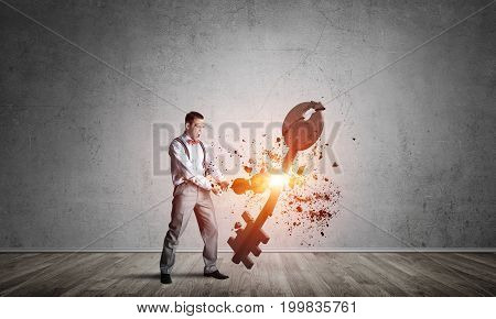Determined businessman in empty interior breaking with violin stone key figure