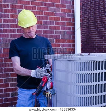 Air Conditioning Repairman Servicing Unit wearing Yellow Hard Hat
