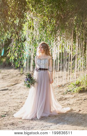 Beautiful Fabulous Blonde Curly Boho Bride With Stylish Rustical Bouquet Standing Under Tree On The