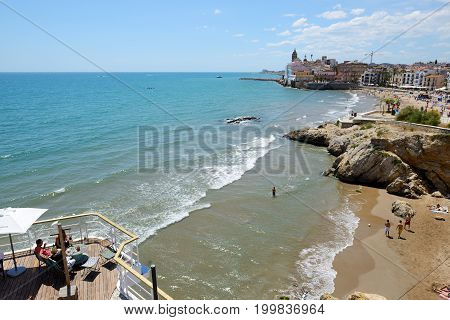 SITGES SPAIN - MAY 23: The tourists enjoiying their vacation on the beach on May 23 2015 in Sitges Spain. Up to 60 mln tourists is expected to visit Spain in year 2015.