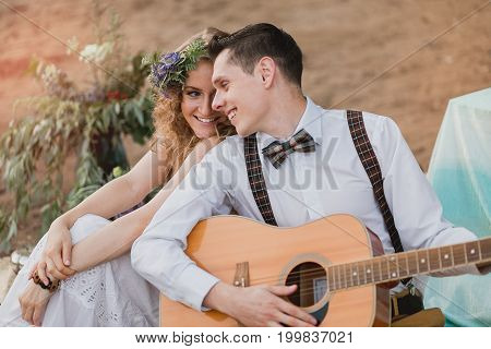 Romantic Couple Sitting Outdoors At Sunset With The Man Playing The Guitar