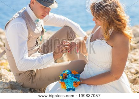 Handsome man putting ring on smiling blonde brides finger at the beach.