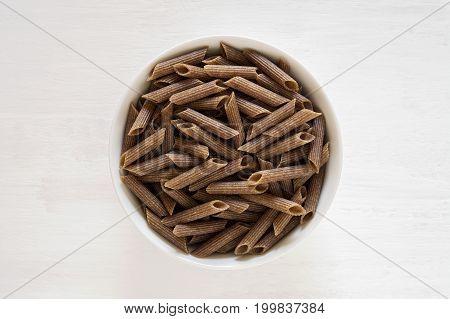 Buckwheat pasta penne in white bowl on white background. Gluten free pasta