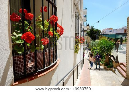 The tourists enjoiying their vacation on side street in Sitges Spain