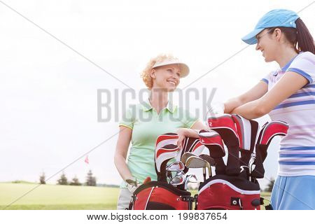 Happy female golfers talking at golf course against clear sky