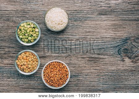 Rice buckwheat peas and lentils in small cups on a wooden surface