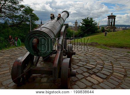 Cannon, monument and city. Edinburgh, Scotland - July 27, 2017 The historic cannon, Dugaland Stewart's monument and the city of Edinburgh seen from Calton Hill.
