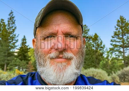 Caucasian Man With White Beard and Green Forest in the Background