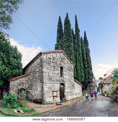 A group of three travelers are walking through the territory of the ancient medieval stone Church. Architectural landmark of Abkhazia - fortress Abaata.