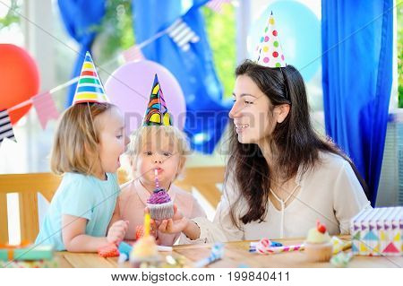 Little child and their mother celebrate birthday party with colorful decoration and cakes