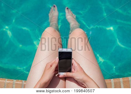High angle view of female using blank screen smartphone at poolside. Technology travel and summer vacation concepts.