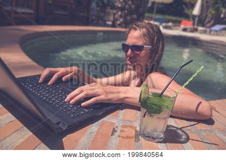 Young female with cocktail working on laptop at the poolside. Freelancer and summer vacation concepts.
