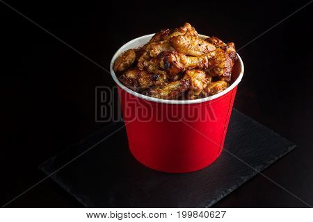 Chicken legs in a bucket. Red bucket is on a slate plate. Fried chicken.