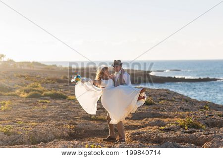 Cheerful married couple standing on the beach.