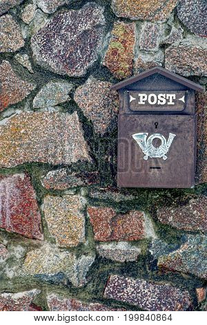 Iron mailbox on a stone wall fence