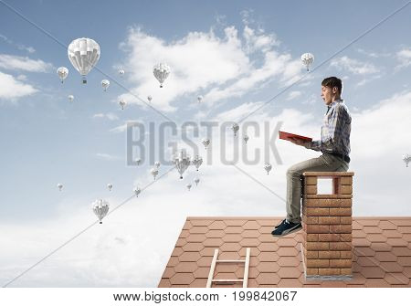 Young man in casual sitting on house chimney with red book in hands