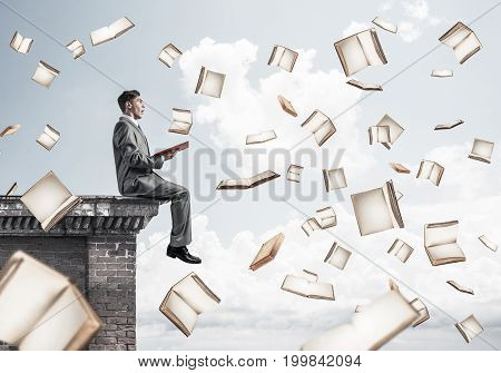 Young businessman sitting on building edge with red book in hands