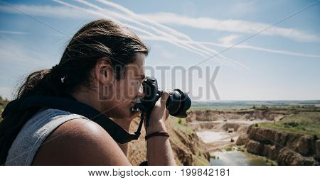 Hipster photographer traveler with long hair taking a shot of beautiful landscape, toned with copy space