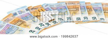 20 and 50 Euro banknotes bills cash with cigarettes. Concept of cost of tabacco cigarettes. Front and top view close-up. Panoramic picture