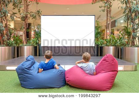 Mock up of blank advertising screen in modern shopping mall. Children looking at big blank digital display