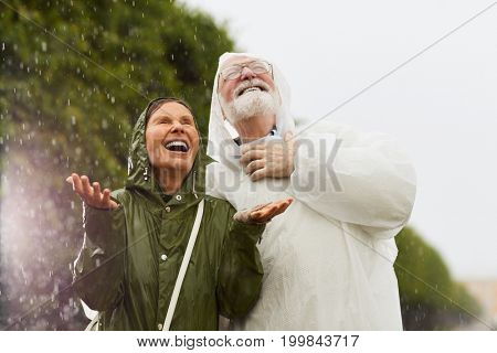 Ecstatic female and her husband in raincoats enjoying rainy weather in natural environment