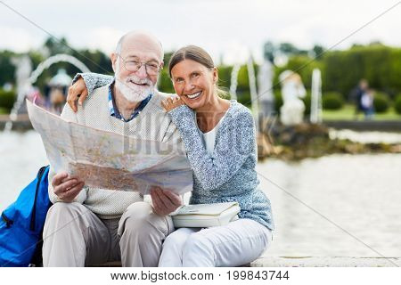 Cheerful aged woman embracing her husband with map guide in urban environment