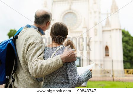Back view of aged couple of tourists sightseeing during journey