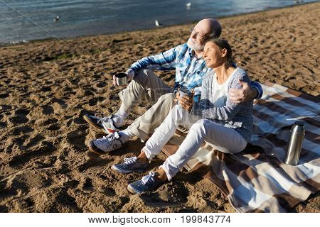 Retired couple taking pleasure in summer evening on the beach