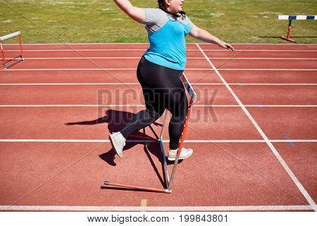 Plus-size woman running down racetrack and bumping into hurdle