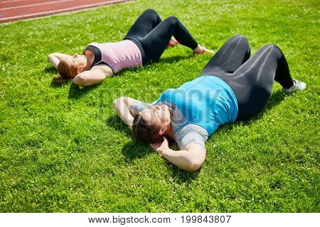 Small group of young active and plump women struggling with overweight on green lawn