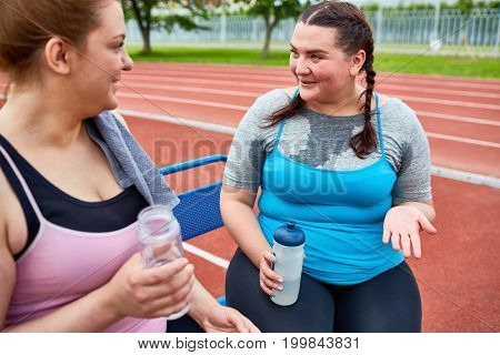Young plump girls discussing their weight-loss results after training